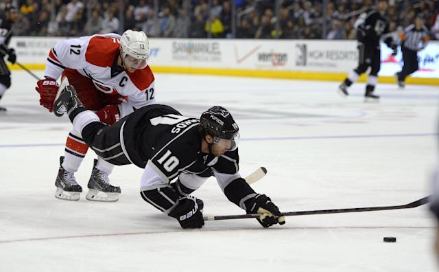 Los Angeles Kings center Mike Richards, front, is tripped by Carolina Hurricanes center Eric Staal during the second period of an NHL hockey game, Saturday, March 1, 2014, in Los Angeles. (AP Photo/Mark J. Terrill)