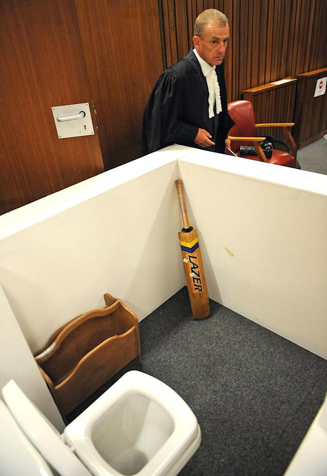 State prosecutor Gerrie Nel, alongside a reconstruction of a toilet cubicle, in court Monday, April 14, 2014, through which Oscar Pistorius shot and killed his girlfriend, Reeva Steenkamp on St. Valentine's day in 2013. The judge temporarily adjourned the murder trial of Pistorius after the athlete started to sob while testifying about the moments before he killed Steenkamp. (AP Photo/Antoine de Ras, Pool)