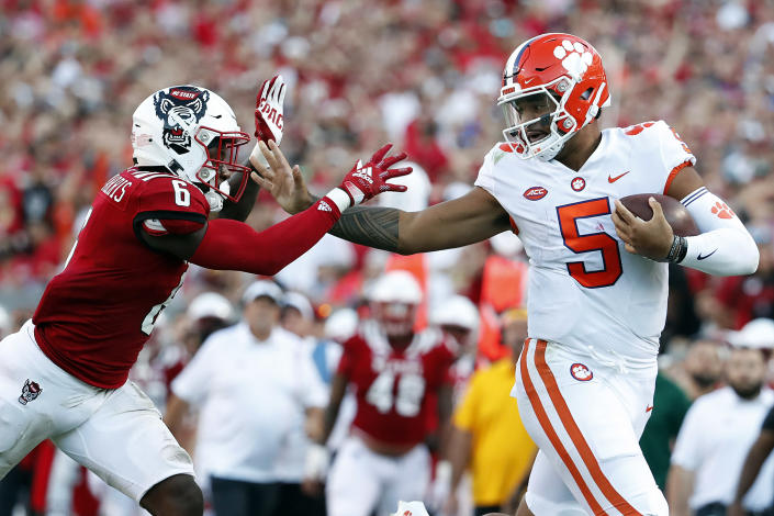 Clemson's D.J. Uiagalelei (5) stiff arms North Carolina State's Jakeen Harris (6) during the second half of an NCAA college football game in Raleigh, N.C., Saturday, Sept. 25, 2021. (AP Photo/Karl B DeBlaker)