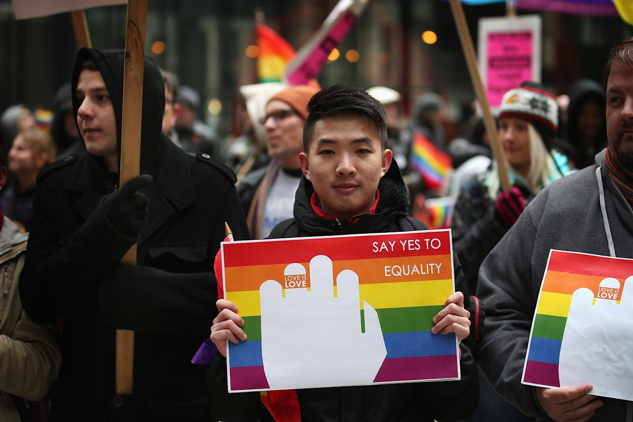 CHICAGO, IL - MARCH 25: Teck Chan (C) participates in a rally in support of gay marriage March 25, 2013 in Chicago, Illinois. The Supreme Court will hear arguments this week in two cases that could determine if states or the federal government can treat same-sex couples and those of the opposite sex differently when recognizing a marriage. The Illinois Senate has approved legislation that will legalize same-sex marriage in the state but it still has to be approved by the Illinois House and signed by Governor Pat Quinn, who has said he supports the legislation. If passed Illinois would become the tenth state to allow same-sex marriage. Thirty states have defined marriage as a union between a man and a woman.  (Photo by Scott Olson/Getty Images)