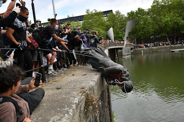 Protesters throw statue of Edward Colston into Bristol harbour during a Black Lives Matter protest rally. (PA)