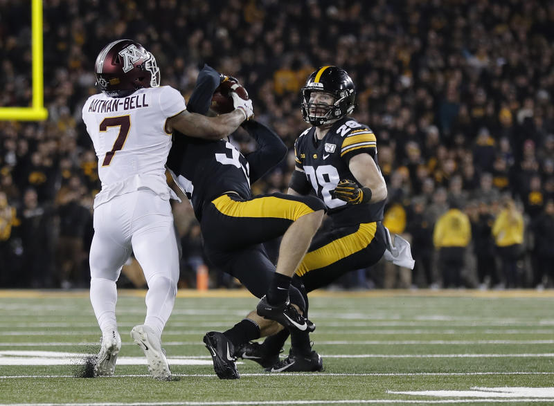 Iowa defensive back Riley Moss, center, intercepts a pass intend for Minnesota wide receiver Chris Autman-Bell, left, as Iowa defensive back Jack Koerner, right, looks on during the second half of an NCAA college football game, Saturday, Nov. 16, 2019, in Iowa City, Iowa. (AP Photo/Matthew Putney)