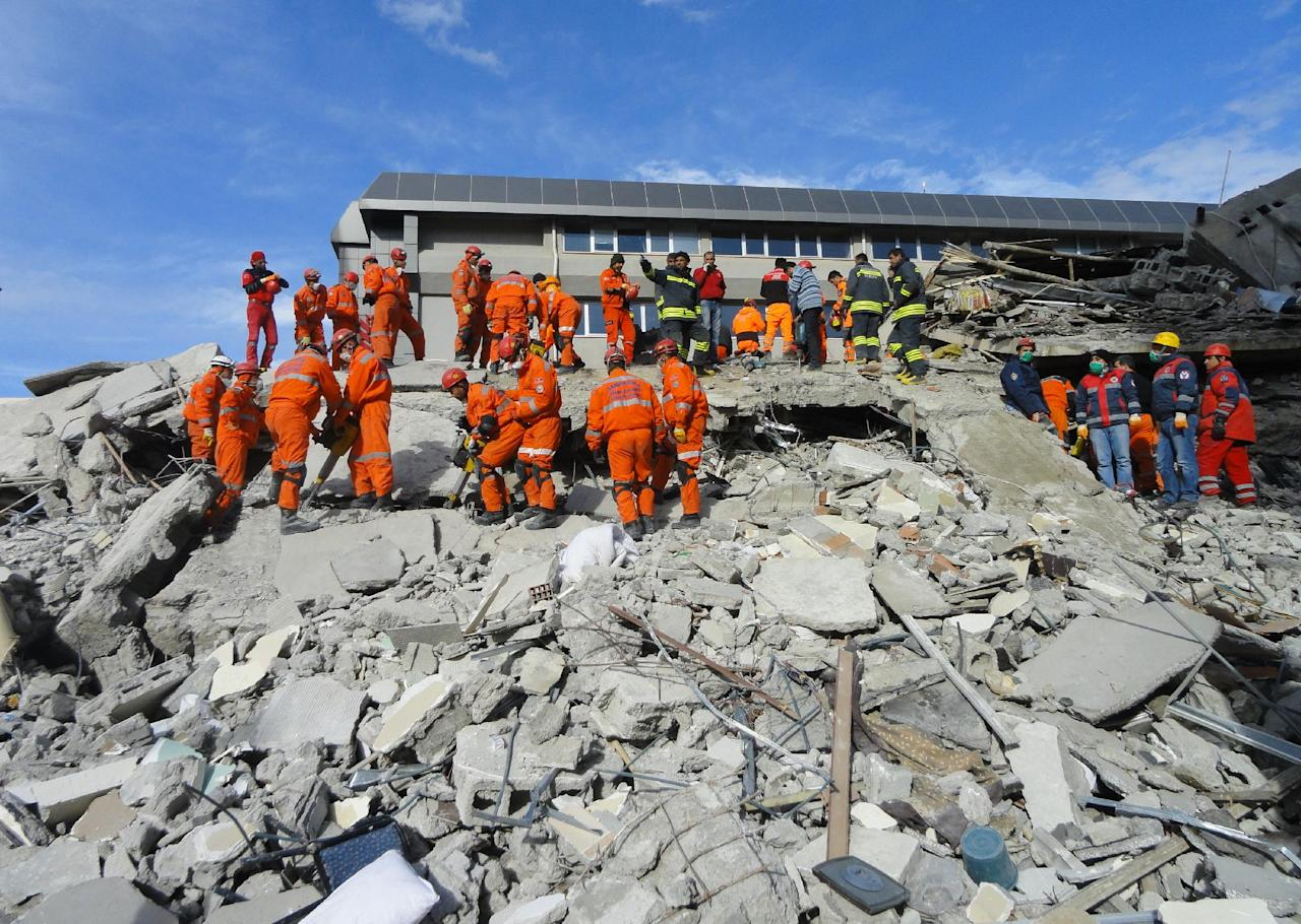 Turkish rescue workers search for survivors in the rubble of a collapsed hotel in Van, Turkey, Thursday, Nov. 10, 2011. Rescuers have pulled out 28 survivors from the rubble of three buildings, collapsed by an earthquake in Van, authorities said. At least ten people, including a Japanese aid worker, were killed and dozens of others trapped. The magnitude-5.7 quake was a grim replay of the previous magnitude-7.2 earthquake that hit Oct. 23, killing more than 600 people.(AP Photo/Bertan Ayduk )