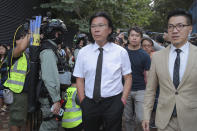 In this Monday, Nov. 25, 2019 photo, lawyer Daniel Wong Kwok-tung, center, arrives at the Polytechnic University to meet the protesters in Hong Kong. Hong Kong national security police on Thursday, Jan. 14, 2021, arrested a lawyer and 10 others on suspicion of helping 12 Hong Kongers try to flee the city, local media reported in the latest arrests in an ongoing crackdown on dissent. Wong, a member of the city's Democratic Party, is known for providing legal assistance to hundreds of protesters arrested during the anti-government protests in Hong Kong in 2019.(AP Photo/Kin Cheung)