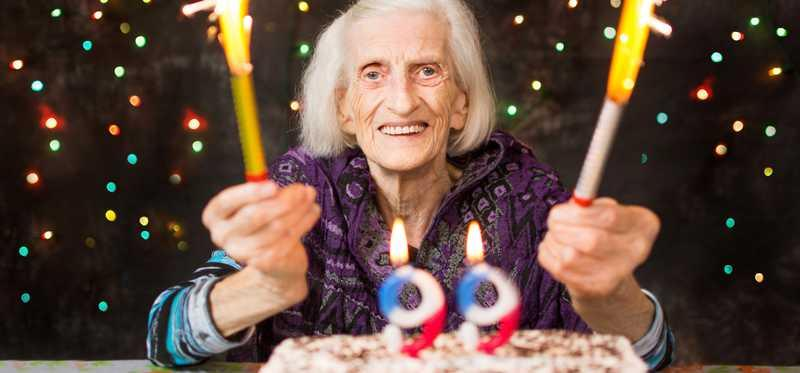 An elderly woman smiling in front of a birthday cake with candles reading ninety-nine.
