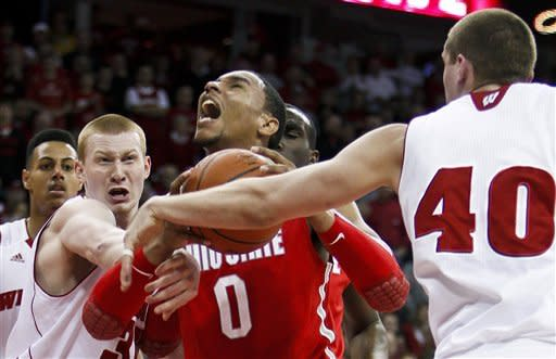 Wisconsin's Mike Bruesewitz, left, fouls Ohio State's Jared Sullinger (0) during the first half of an NCAA college basketball game Saturday, Feb. 4, 2012, in Madison, Wis. At right is Wisconsin's Jared Berggren. (AP Photo/Andy Manis)
