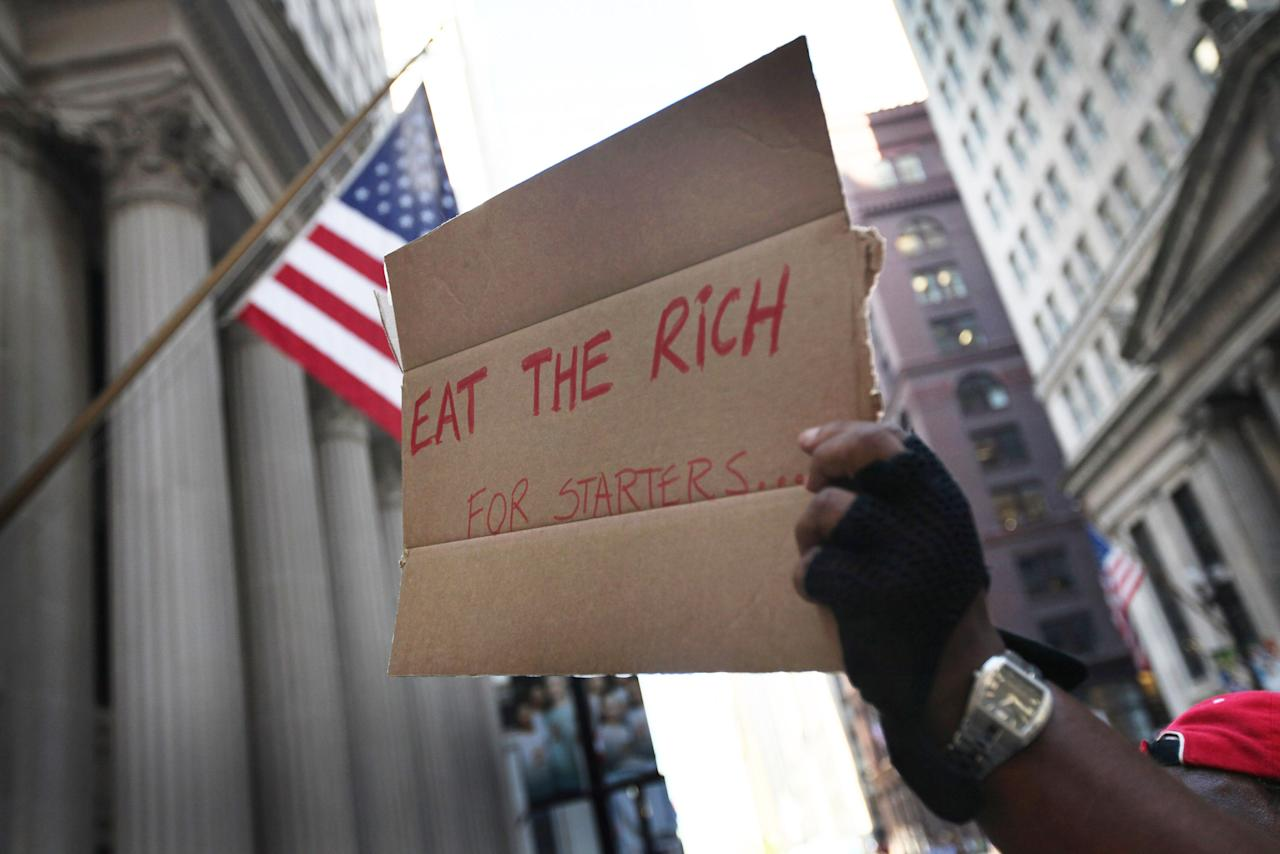 A demonstrator with Occupy Chicago holds up a sign outside the Federal Reserve Bank building October 5, 2011 in Chicago, Illinois. The protest is one of many around the country being held in solidarity with the Occupy Wall Street protests currently taking place in New York City. Among the things that demonstrators are protesting is what they believe is greed and corruption among banking and business leaders. (Photo by Scott Olson/Getty Images)