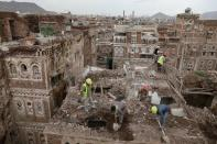 Workers demolish a building damaged by rain in the UNESCO World Heritage site of the old city of Sanaa