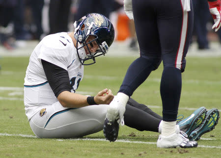 FILE PHOTO: Jacksonville Jaguars quarterback Blaine Gabbert examines his arm after being sacked by Houston Texans safety Danieal Manning forcing a turnover during their NFL football game in Houston November 18, 2012. Gabbert was injured on the play and was taken out of the game. REUTERS/Richard Carson
