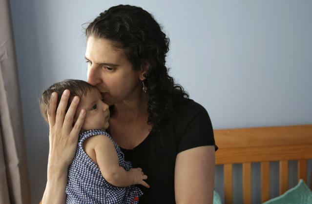 A woman holds her eight-week-old baby in Providence, R.I. After she had her second daughter in April of 2017, she was able to use Rhode Island's paid family leave program, which started in 2014 and covers four weeks of partial pay. (AP Photo/Steven Senne)