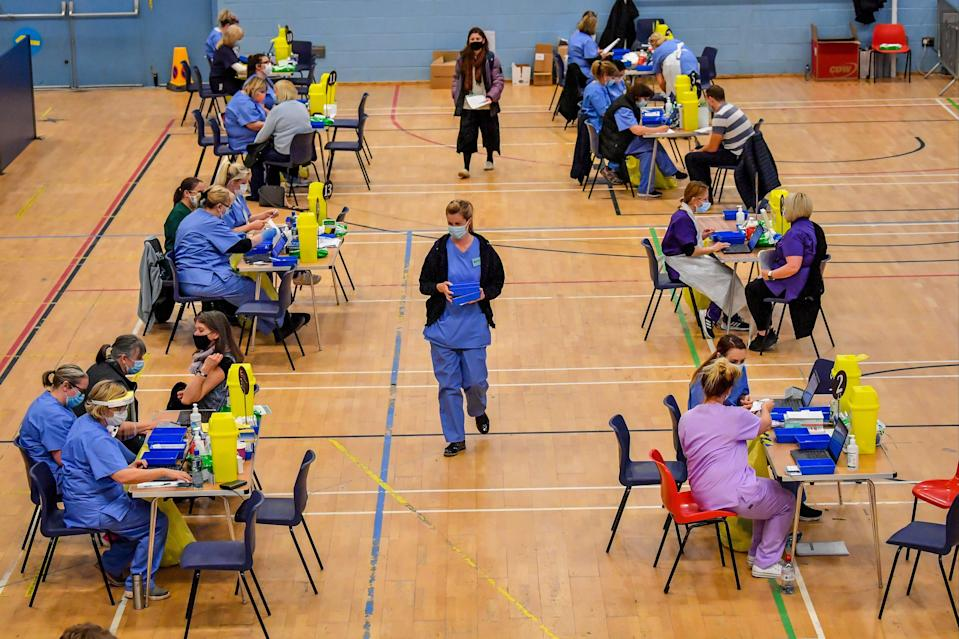 <p>Stations are set up where care workers give out injections of the Pfizer jab at Cwmbran Stadium, south Wales</p> (PA)
