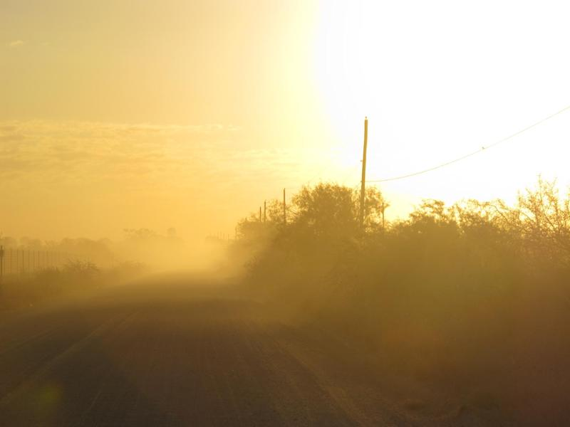 The sun rises along the stretch of gravel road near La Joya, Texas, Friday Oct. 26, 2012, where a Texas Department of Public Safety helicopter and sharpshooter assisted the previous day in the chase of a suspected illegal immigrant smuggler. Two people in the fleeing vehicle were killed and a third was wounded. (AP Photo/Chris Sherman)
