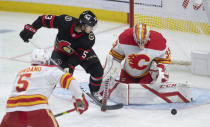 Ottawa Senators' Matthew Peca pressures Calgary Flames goaltender David Rittich as he makes a save during the first period of an NHL hockey game Thursday, Feb. 25, 2021, in Ottawa, Ontario. (Adrian Wyld/The Canadian Press via AP)