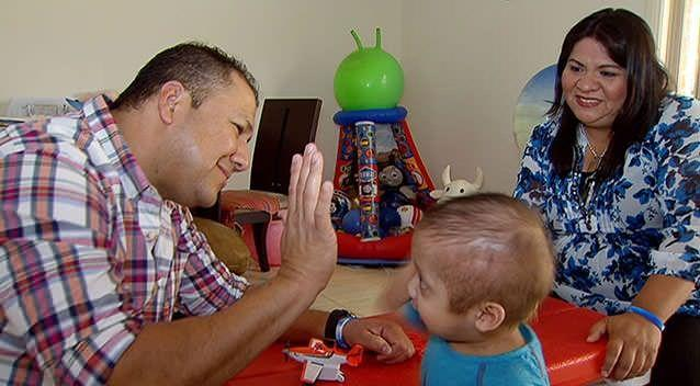 Enzo gives his dad Percy a high-five while his mum Catherina looks on. Photo: 7News.