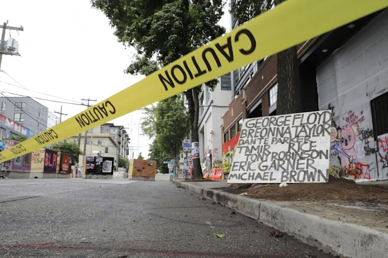 Caution tape is shown near a sign with the names of victims of police violence, Saturday, June 20, 2020, at the Capitol Hill Occupied Protest zone in Seattle. It is unknown who put the tape in place. A pre-dawn shooting near the area left one person dead and critically injured another person, authorities said Saturday. The area has been occupied by protesters after Seattle Police pulled back from several blocks of the city's Capitol Hill neighborhood near the Police Department's East Precinct building. (AP Photo/Ted S. Warren)