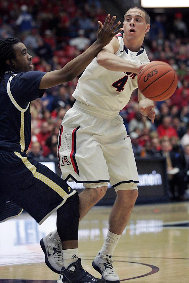 Arizona's T.J. McConnell (4) passes against the defense of Northern Arizona's Aaseem Dixon, left, during the first half of an NCAA college basketball game Monday, Dec. 23, 2013, in Tucson, Ariz. (AP Photo/John MIller)