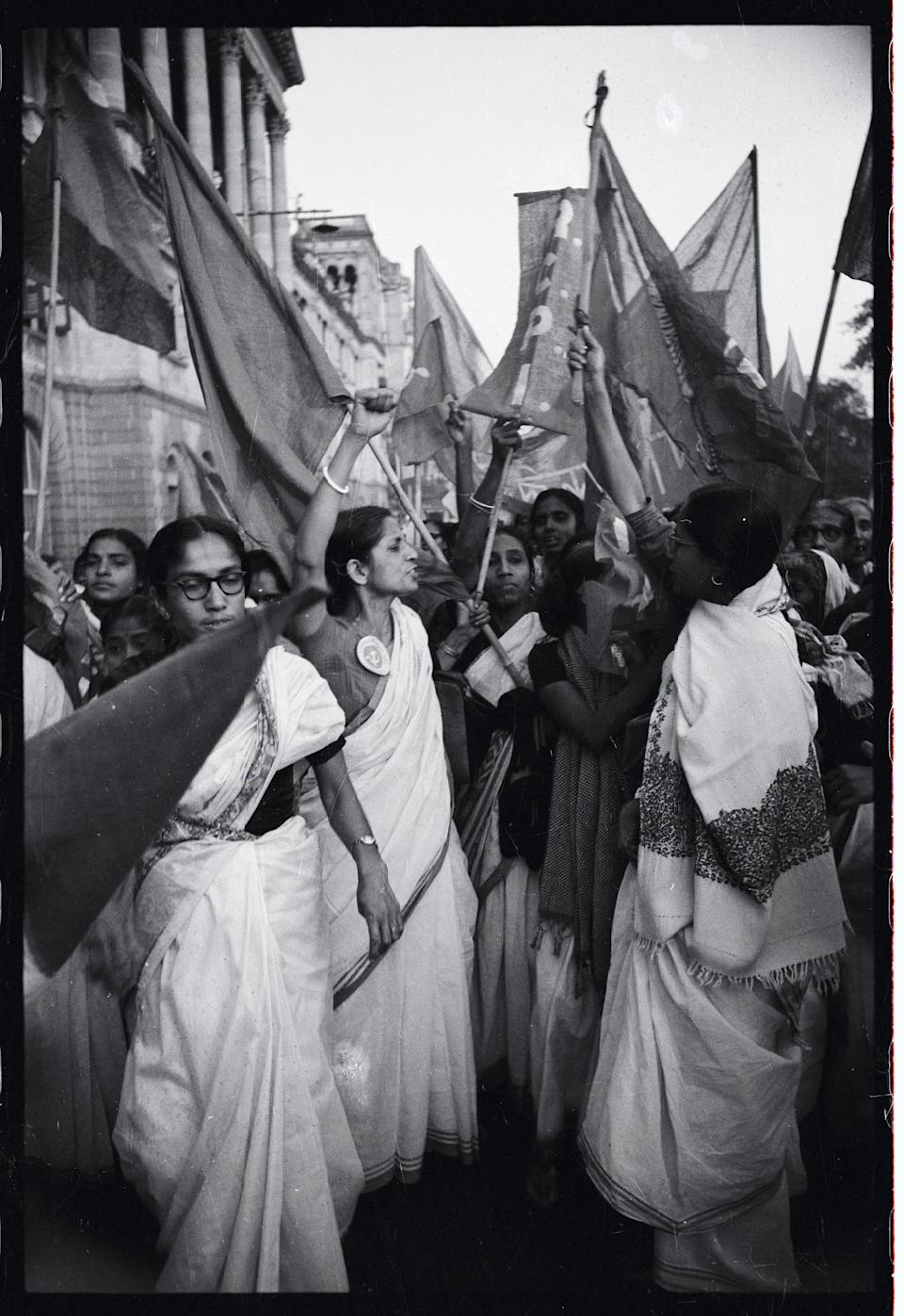 (Original Caption) Flag-carrying, hand-waving, enthusiastic women shout anti-government slogans during a United Front women's Day Demonstration here recently. More than 500 of the active ladies in Calcutta and an equal number in other West Bengal State Districts were arrested for defying the existing ban on public assembly anywhere in the states. The woman in the center wears a button sporting a hammer and sickle, symbol of the Soviet Union.