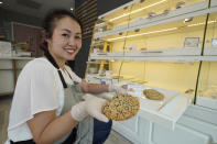 Pastry chef Elaine Lau holds a Dim Sum Cookie at the Sunday Bakeshop in Oakland, Calif., Thursday, Aug. 19, 2021. From ube cakes to mochi muffins, bakeries that sweetly encapsulate what it is to grow up Asian and American have been popping up more in recent years. Their confections are a delectable vehicle for young and intrepid Asian Americans to celebrate their dual identity. (AP Photo/Eric Risberg)