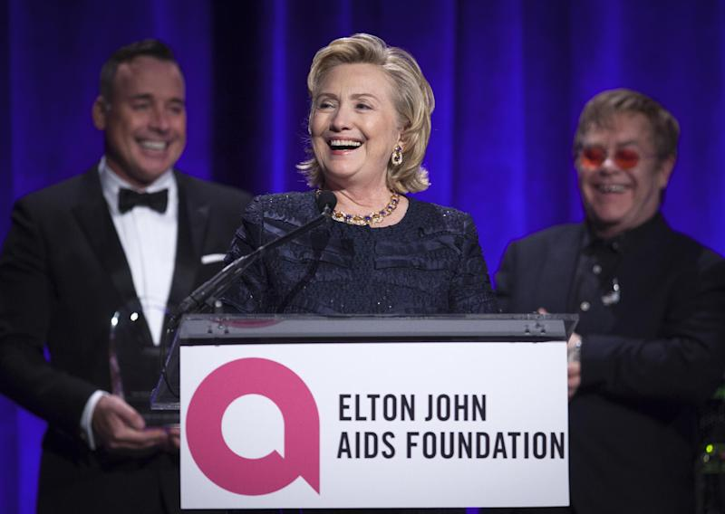 "Former Secretary of State Hillary Clinton speaks as Elton John, right, and his partner David Furnish look on, after receiving her Founders award during the Elton John AIDS Foundation's 12th Annual ""An Enduring Vision"" benefit gala at Cipriani Wall Street on Tuesday, Oct. 15, 2013 in New York. (Photo by Carlo Allegri/Invision/AP)"