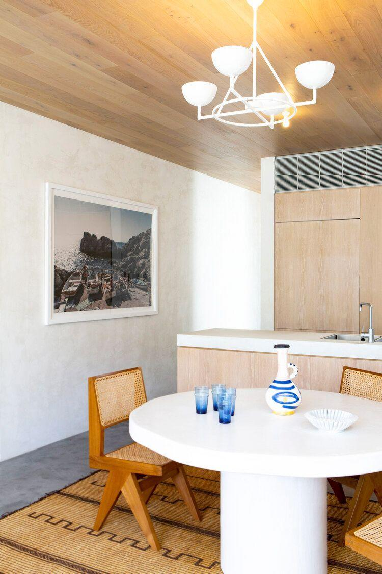 """<p>From the polished concrete floors to the plaster walls and wood paneled ceiling, this open plan dining room and kitchen by <a href=""""https://tamsinjohnson.com/"""" rel=""""nofollow noopener"""" target=""""_blank"""" data-ylk=""""slk:Tamsin Johnson"""" class=""""link rapid-noclick-resp"""">Tamsin Johnson</a> is a texturally rich oasis. And the mix of raw materials with a more soft and serene color scheme along with laidback furniture strikes the ideal balance for a modern and edgy yet classic coastal escape. </p>"""