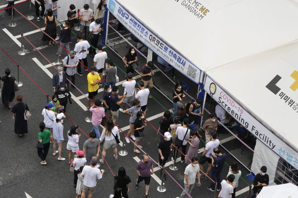 """People queue in line to wait to get coronavirus testing at a Public Health Center in Seoul, South Korea, Sunday, July 11, 2021. The banner reads: """"Quick scan with QR Code."""" (AP Photo/Ahn Young-joon)"""