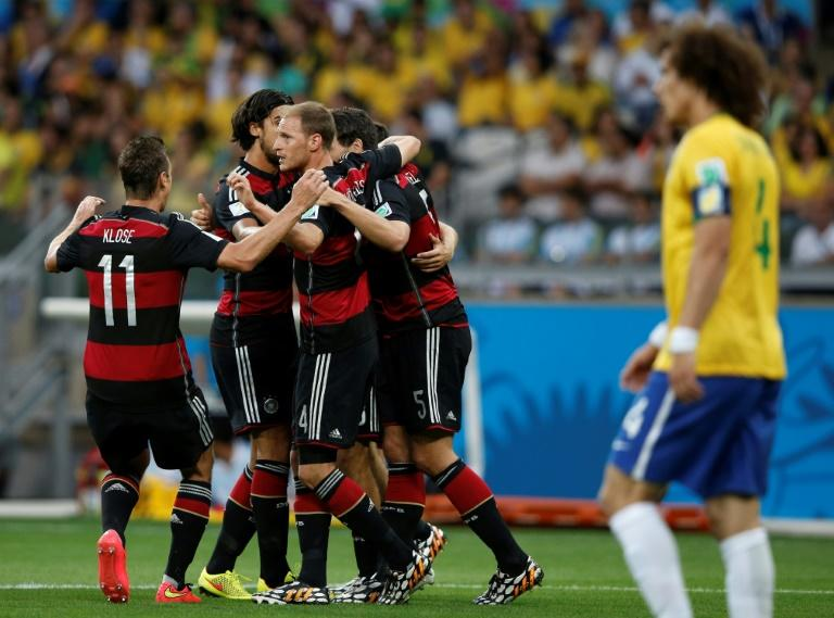Germany players celebrate after Thomas Mueller opens the scoring against Brazil as a forlorn David Luiz looks on disconsolately