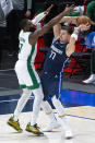Dallas Mavericks guard Luka Doncic (77) looks to pass the ball as Boston Celtics guard Jaylen Brown (7) defends during the first half of an NBA basketball game in Dallas, Tuesday, Feb. 23, 2021. (AP Photo/Sam Hodde)