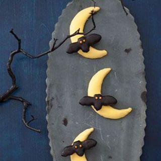 """<p>Don't fret about making your own cookies from scratch. Simply cut out bat and moon shapes from soft chocolate chip cookies and decorate them!</p><p><a href=""""https://www.womansday.com/food-recipes/food-drinks/recipes/a11390/bats-flying-across-the-moon-cookies-recipe-122707/"""" rel=""""nofollow noopener"""" target=""""_blank"""" data-ylk=""""slk:Get the Bats Flying Across the Moon Cookies recipe."""" class=""""link rapid-noclick-resp"""">Get the Bats Flying Across the Moon Cookies recipe. </a> </p>"""