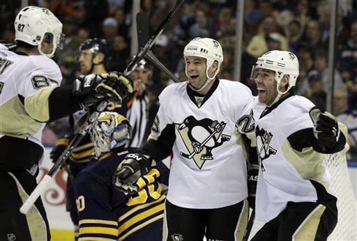 Pittsburgh Penguins' Steve Sullivan (26) celebrates his goal with teammates Sidney Crosby (87) and Pascal Dupuis (9) on Buffalo Sabres goalie Ryan Miller during the second period of an NHL hockey game in Buffalo, N.Y., Friday, March 30, 2012. The Penguins won 5-3. (AP Photo/David Duprey)