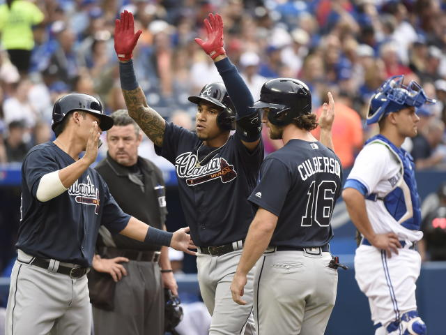 Atlanta Braves' Johan Camargo, center, celebrates with teammates Kurt Suzuki, left, and Charlie Culberson (16) after hitting a grand slam as Toronto Blue Jays catcher Luke Maile waits during the second inning of a baseball game Tuesday, June 19, 2018, in Toronto. (Nathan Denette/The Canadian Press via AP)