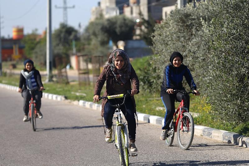 Assalah Abu Sharkh (centre), Sarah Sleibi (right), and Nour Sleibi ride their bicycles on a road in Beit Hanun (AFP Photo/Mohamed Abed)