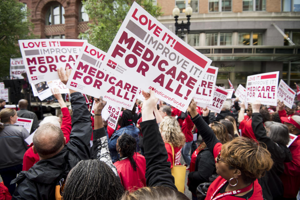 """UNITED STATES - APRIL 29: Members of National Nurses United union members wave """"Medicare for All"""" signs during  a rally in front of the Pharmaceutical Research and Manufacturers of America in Washington calling for """"Medicare for All"""" on Monday, April 29, 2019.  (Photo By Bill Clark/CQ Roll Call)"""