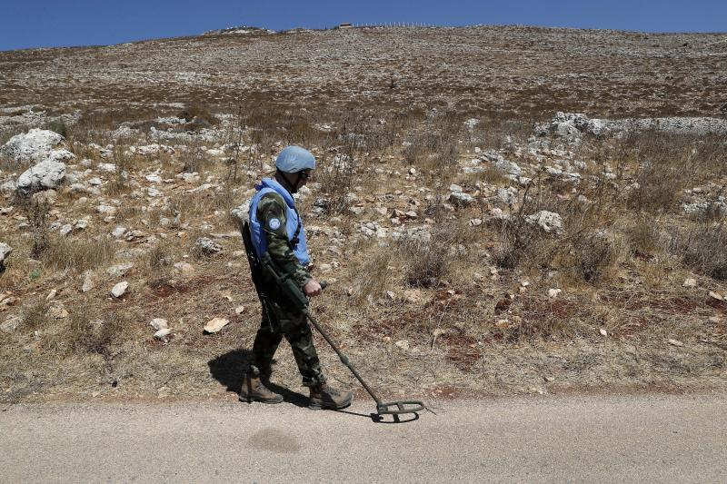 Irish UN peacekeepers use mine detectors as they patrol near the fields struck by Israeli army shells in the southern Lebanese-Israeli border village of Maroun el-Ras, Lebanon, Monday, Sept. 2, 2019. The Lebanon-Israel border was mostly calm with U.N. peacekeepers patrolling the border Monday, a day after the Lebanese militant Hezbollah group fired a barrage of anti-tank missiles into Israel, triggering Israeli artillery fire that lasted less than two hours and caused some fires. (AP Photo/Hussein Malla)