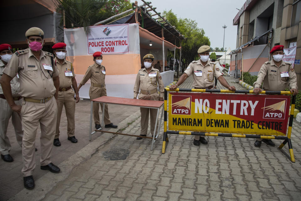 Assam police personnel stand guard near a counting hall during the counting of votes of Assam state assembly election in Gauhati, India, Sunday, May 2, 2021. With Indian hospitals struggling to secure a steady supply of oxygen, and more COVID-19 patients dying amid the shortages, a court in New Delhi said it would start punishing government officials for failing to deliver the life-saving items. (AP Photo/Anupam Nath)