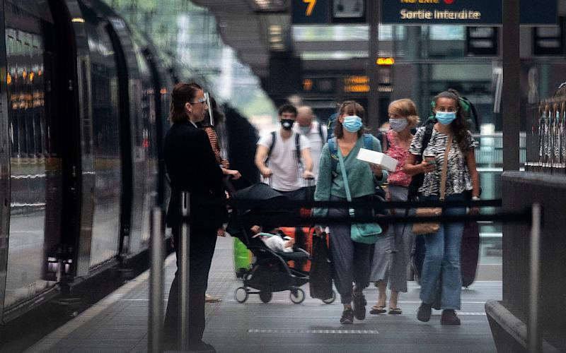 Travellers wearing face masks arrive from Paris to St Pancras Station in London after quarantine restrictions were imposed at 4am on Saturday morning -  Victoria Jones / PA
