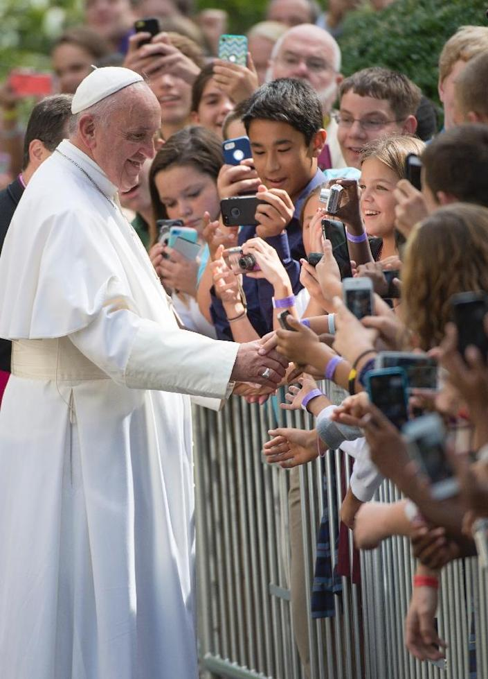 Pope Francis greets well-wishers at the Apostolic Nunciature to the United States upon returning from his trip to Capitol Hill, on September 24, 2015 (AFP Photo/Molly Riley)