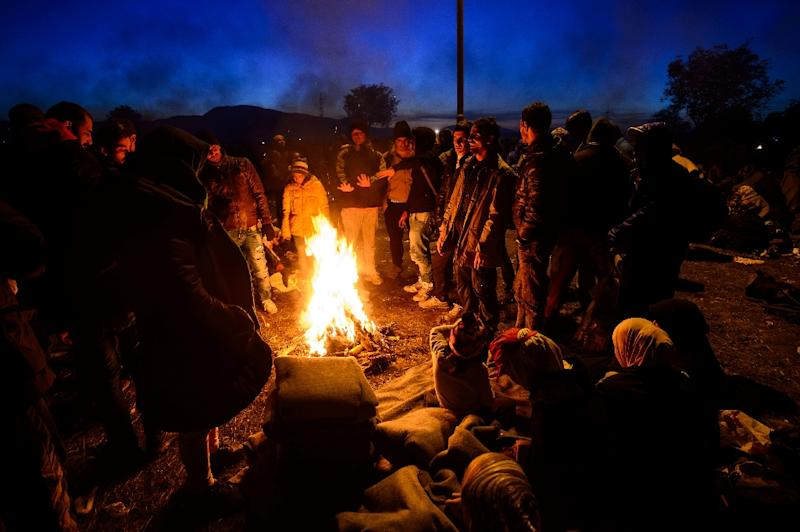 Migrants and refugees gather around a bonfire to warm themselves as they wait to be transported to a refugee center after crossing the Croatian-Slovenian border near Rigonce, Slovenia, on October 24, 2015 (AFP Photo/Jure Makovec)