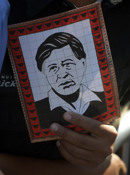 An attendee holds a picture of Cesar E. Chavez as President Barack Obama speaks as to announce the establishment of the Cesar E. Chavez National Monument, Monday, Oct. 8, 2012, in Keene, Calif. The property is recognized worldwide for its historic link to civil rights icon Cesar Chavez and the farm worker movement. (AP Photo/Mark J. Terrill)