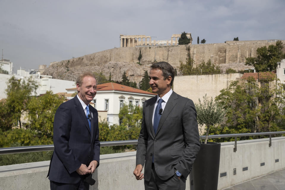 Microsoft President Brad Smith, left, speaks with Greek Prime Minister Kyriakos Mitsotakis during a ceremony held in the Acropolis Museum, in the background is the ancient Parthenon temple, central Athens, on Monday, Oct. 5, 2020. Microsoft has announced plans to build three data centers in greater Athens, providing a badly needed investment of up to $1 billion to the Greek economy which has been hammered by the pandemic. (AP Photo/Petros Giannakouris)