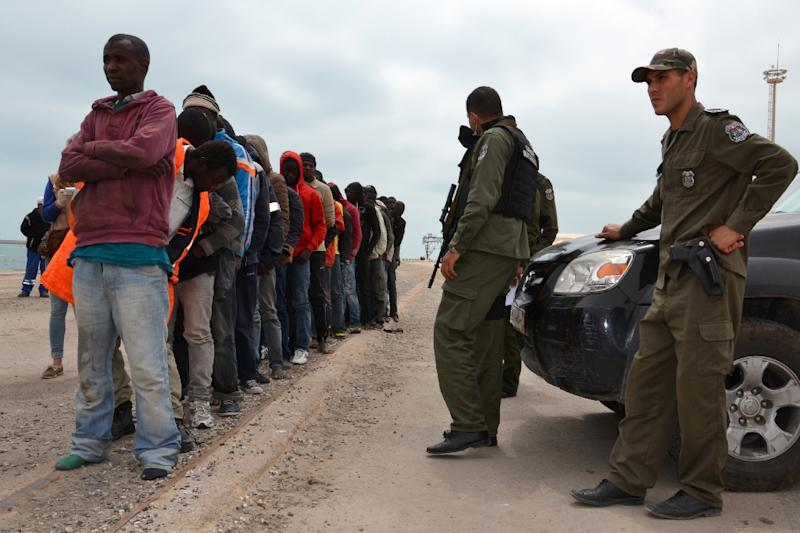 Migrants stand next to Tunisian security forces in the southeastern port of Zarzis on April 25, 2015, after they were rescued by fishermen while trying to sail from Libya to Europe (AFP Photo/Fethi Nasri)