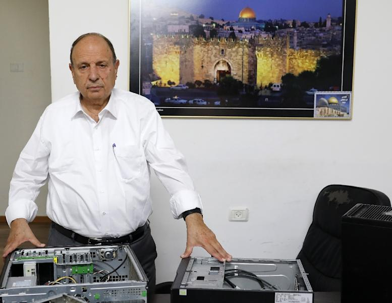 The minister in charge of Jerusalem affairs for the Palestinian Authority, Adnan al-Husseini, poses in front of gutted computers after an Israeli raid in the occupied West Bank town of Al-Ram, near Jerusalem (AFP Photo/Ahmad GHARABLI)