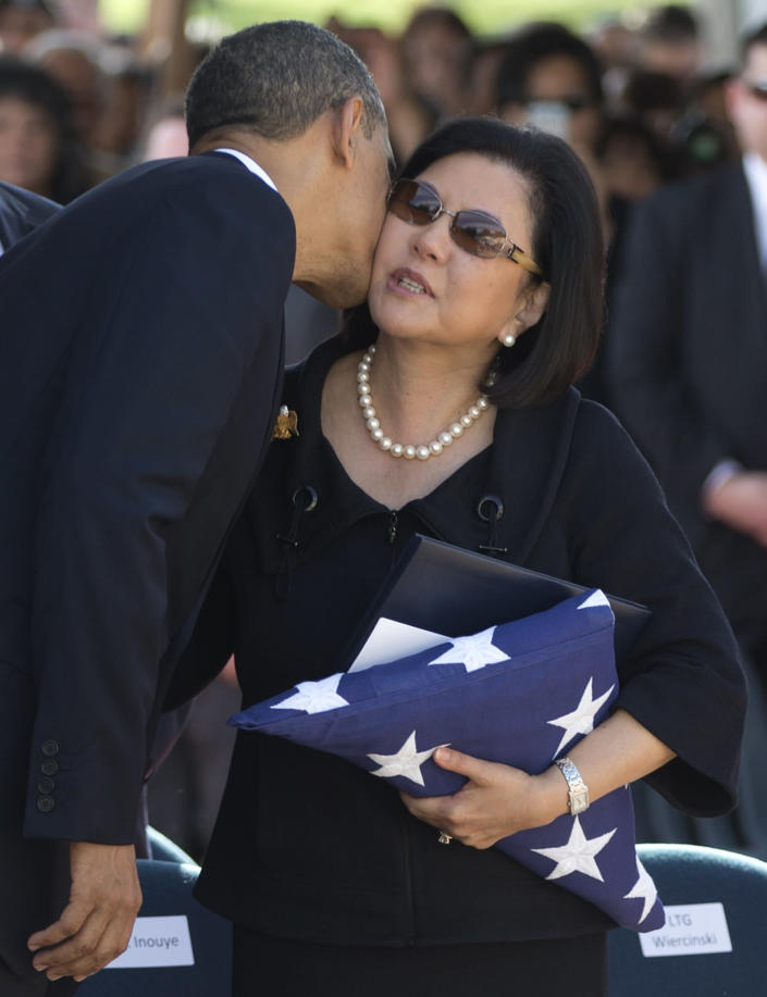 FILE - In this Dec. 23, 2012 file photo President Barack Obama kisses Irene Hirano Inouye, the widow of the late U.S. Sen. Daniel Inouye, as she holds the flag that was draped over her husband's casket during a memorial service at the National Memorial Cemetery of the Pacific in Honolulu. Hirano Inouye, the widow of the late U.S. Sen. Daniel K. Inouye of Hawaii and the founding CEO of the Japanese American National Museum in Los Angeles, has died in Los Angeles on Tuesday, April 7, 2020, after an extended illness. She was 71. Hirano Inouye had most recently served as president of the U.S.-Japan Council, which aims to develop and connect leaders to strengthen the U.S.-Japan relationship. (AP Photo/Carolyn Kaster, File)