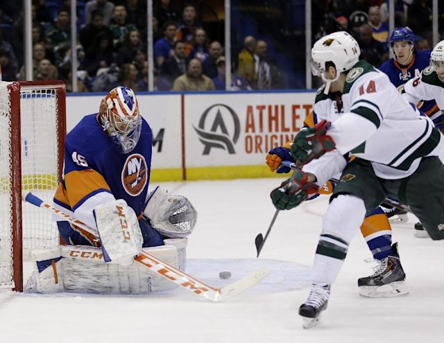 New York Islanders goalie Anders Nilsson, left, makes a save during the first period of the NHL hockey game against the Minnesota Wild, Tuesday, March 18, 2014, in Uniondale, New York. (AP Photo/Seth Wenig)