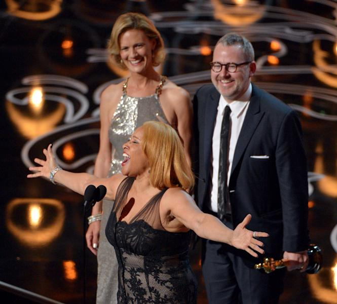 "Darlene Love, center, sings as Janet Friesen, background left, and Morgan Neville accept the award for best documentary feature for ""20 Feet from Stardom"" during the Oscars at the Dolby Theatre on Sunday, March 2, 2014, in Los Angeles. (Photo by John Shearer/Invision/AP"