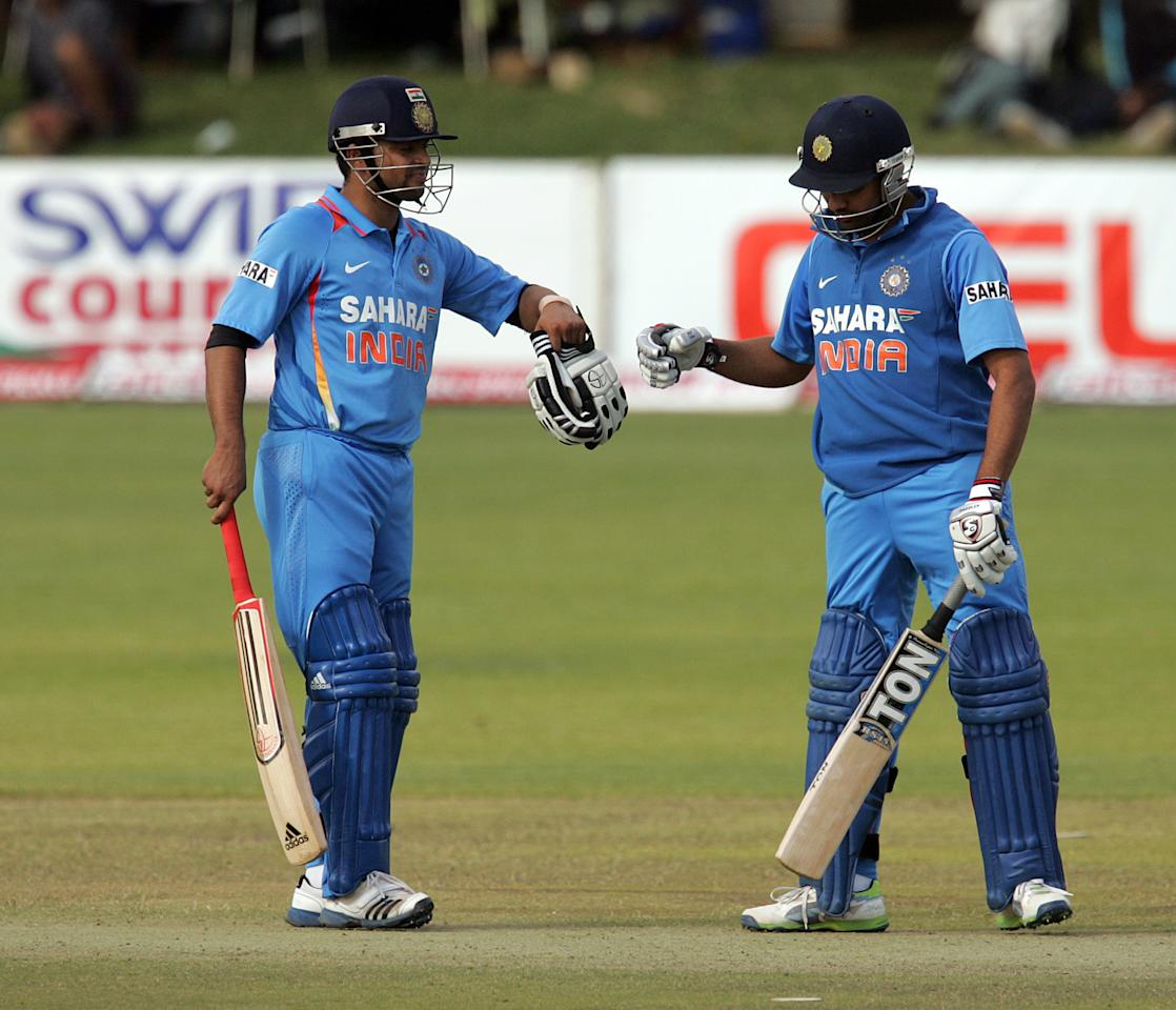 Indian batsman Suresh Raina (L)  and Rohit Sharma (R) celebrate a good partnership during the 4th match of the 5-match cricket ODI series between Zimbabwe and India at Queen's Sports Club in Harare on August 1, 2013. AFP PHOTO / Jekesai Njikizana        (Photo credit should read JEKESAI NJIKIZANA/AFP/Getty Images)