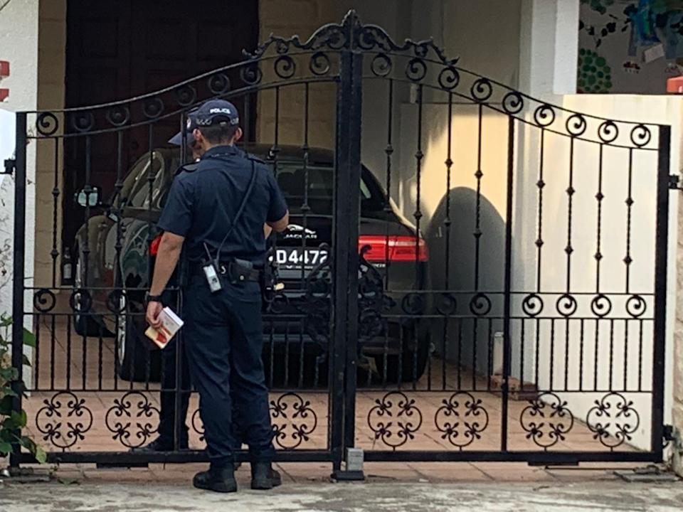 Two police officers at 7 Galistan Avenue, the premises used by Platinium Dogs Club for its pet boarding services. A woman who is said to be linked to Platinium is sitting inside the car, according to eyewitness Derrick Tan. PHOTO: Derrick Tan