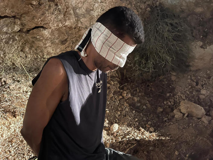In this photo provided by Israel Police, Zakaria Zubeidi, one of the six Palestinians who escaped from a high-security prison earlier this week, is blindfolded after being recaptured in the Arab town of Umm al-Ghanam, northern Israel, Saturday, Sept. 11, 2021. Israeli police on Saturday said they have arrested four of the six Palestinians who broke out of a maximum-security prison this week including Zubeidi, a famed militant leader whose exploits over the years have made him a well-known figure in Israel. (Israeli Police via AP)