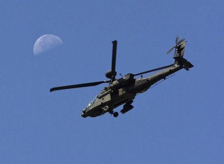 A U.S. Army Apache flies past the moon in the Zharay district of Kandahar province