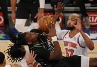 Naz Reid, left, of the Minnesota Timberwolves looks to shoot as Taj Gibson, right, of the New York Knicks defends during the first half of an NBA basketball game Sunday, Feb. 21, 2021, in New York. (Sarah Stier/Pool Photo via AP)