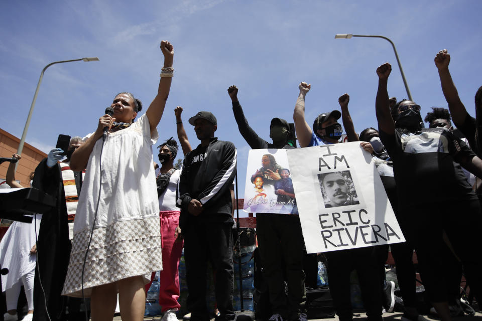 FILE - In this June 8, 2020, file photo, Melina Abdullah, left, of Black Lives Matter Los Angeles, leads a crowd in a raising of fists in Los Angeles during a protest over the death of George Floyd who died May 25 after he was restrained by Minneapolis police. The Black Lives Matter Global Network Foundation, which grew out of the creation of the Black Lives Matter movement, is formally expanding a $3 million financial relief fund that it quietly launched in February 2021, to help people struggling to make ends meet during the ongoing coronavirus pandemic. (AP Photo/Marcio Jose Sanchez, File)